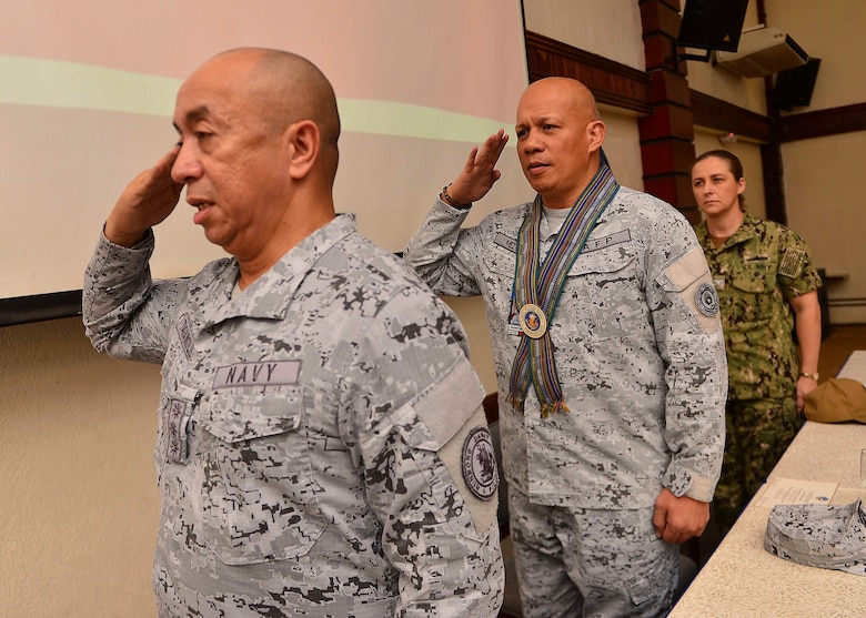 PUERTO PRINCESA, Philippines (Oct. 21, 2019) - (From left to right) Philippine Navy Capt. Francisco Tagamolila Jr., acting commander, Philippine Naval Forces West, Philippine Navy Vice Adm. Rene Medina, commander, Western Command, and U.S. Navy Capt. Ann McCann, deputy commodore of Destroyer Squadron 7, stand together on stage for the playing of the Philippine national anthem during the closing ceremony for Maritime Training Activity (MTA) Sama Sama 2019. Now in its third year, MTA Sama Sama includes forces from Japan, Philippines and the United States, and is designed to promote regional security cooperation, maintain and strengthen maritime partnerships, and enhance maritime interoperability.