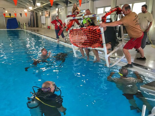 Soldiers with the 28th Expeditionary Combat Aviation Brigade prepare to be submerged in a Shallow Water Egress Trainer chair, pushed by civilian and military instructors. The Soldiers had to demonstrate water survival skills, simulating exiting a submerged helicopter, during training at the pool at Somerset Area High School Oct. 19, 2019.