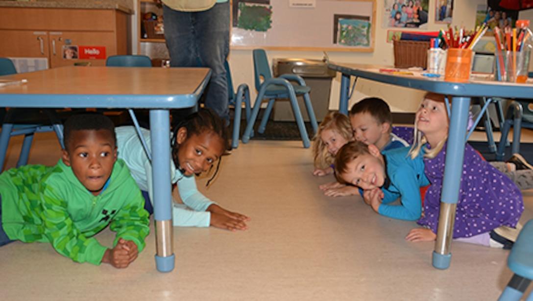 Children practice earthquake drill