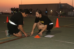 Staff Sgt. Eileen Crandall, 103rd Expeditionary Sustainment Command (ESC), helps mark the distance during standing power throw event of the Army Combat Fitness Test (ACFT) at Camp Arifjan, Kuwait, Oct. 16, 2019. Crandall, one of two master fitness trainers in the 103rd ESC, said the program has greatly enhanced the unit's capabilities to comply with the Army standard of administering the new ACFT to all Soldiers in the formation by October, 2020.