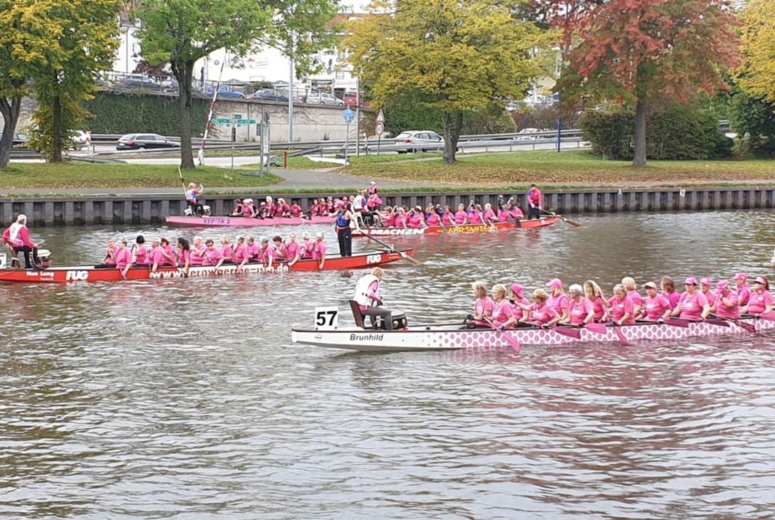three dragon boat teams paddle in the water