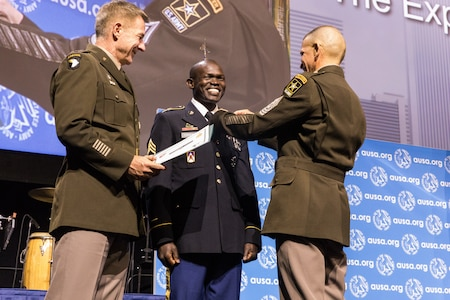 Sgt. 1st Class Anthony Lodiong receives his Expert Soldier Badge from Army Chief of Staff Gen. James C. McConville and Sgt. Maj. of the Army Michael A. Grinston at the at the Eisenhower Luncheon during the Association of the United States Army annual meeting and exposition at the Walter E. Washington Convention Center in Washington, D.C. Oct. 14. (Photo courtesy of the U.S. Army)