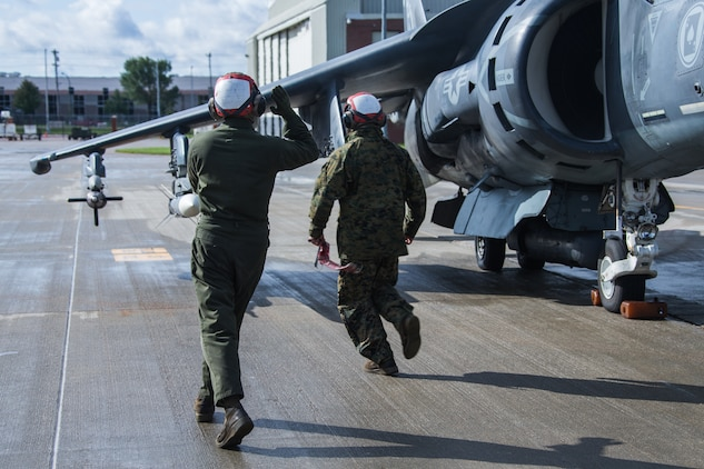 Lance Cpl. Fabian Vigil (left) and Lance Cpl. Jacob A. Fox prepare an AV-8B II Harrier attack jet for take-off during a training mission with the 175th Fighter Squadron, 114th Fighter Wing at Joe Foss Field, Sioux Falls, S.D, Oct. 5, 2019. Marine Attack Squadron 231 and 175th FS, 114th FW are participating in force-on-force training consisting of simulated air-to-air combat and air-to-ground strikes to enhance interoperability and readiness. Fabian and Fox are aircraft ordnance technicians with VMA-231. (U.S. Marine Corps photo by Lance Cpl. Gavin Umboh)