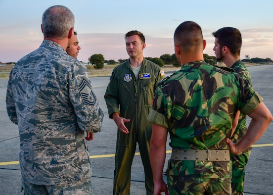 Senior Airman Caleb Bowlick, a 700th Airlift Squadron loadmaster (center) speaks with Chief Master Sgt. Mark Carlisle (left), 94th Aircraft Maintenance Squadron superintendent, and members of the Portuguese air force on the flight line during Exercise Real Thaw 2019 at Beja Air Base, Beja, Portugal, Oct. 2, 2019. Real Thaw is a Portuguese-led multi-lateral flying training exercise intended to build trust and interoperability between NATO allies. (U.S. Air Force photo/Senior Airman Justin Clayvon)