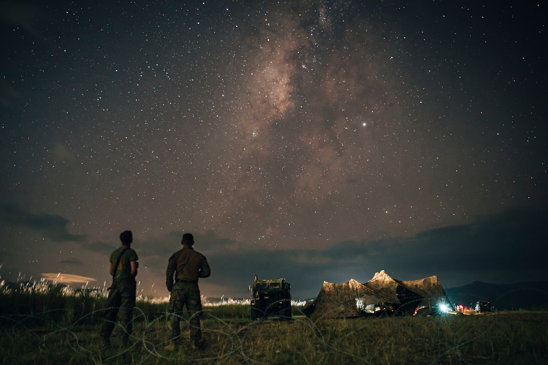 U.S. Marine Corps Lance Cpl. Davon Moore, left, a field artillery cannoneer, and Gunnery Sgt. Nicholas Cantu, the motor transportation chief, both with Alpha Battery, Battalion Landing Team 3/5, 11th Marine Expeditionary Unit, observe the night sky at Colonel Ernesto Ravina Air Base, Philippines, during exercise KAMANDAG 3, Oct. 16, 2019. KAMANDAG advances military modernization and capability development through subject matter expert exchanges.