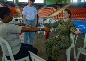 A U.S. Navy Hospital Corpsman teaches a woman exercises.
