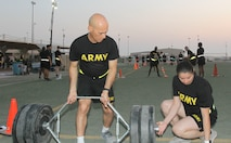 Sgt. 1st Class John Santos, 1st Theater Sustainment Command (TSC), helps prepare equipment for the 3 repetition maximum deadlift event of the Army Combat Fitness Test (ACFT) at Camp Arifjan, Kuwait, Oct. 16, 2019. Sgt. 1st Class John Santos established this program to help expand the force of ACFT administrators and graders throughout Camp Arifjan. Since June, 2019, Santos has trained about 225 Soldiers to administer the ACFT.