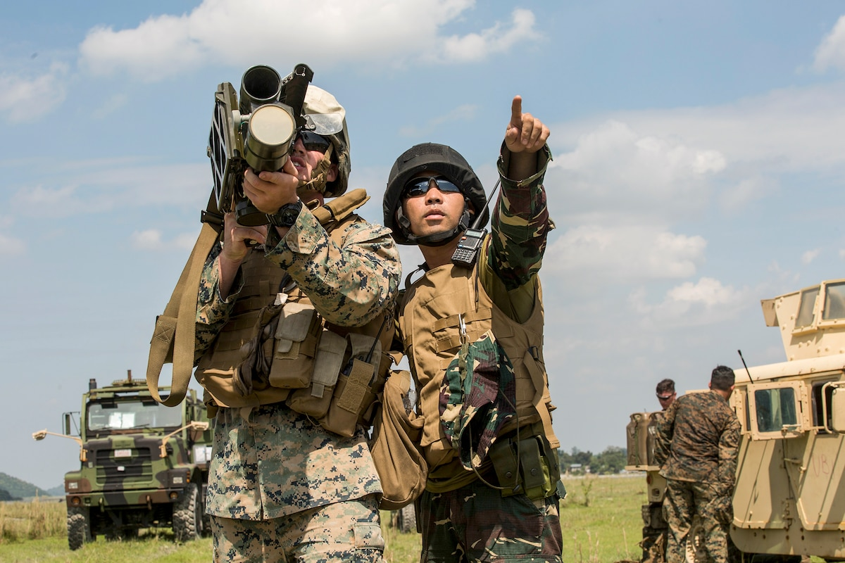 A Marine aims a weapon as a Philippine service member points into the distance.