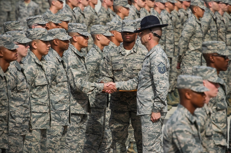 A military training instructor, center right, presents an Airmen's coin to one of his newly graduated trainees during the coin ceremony and retreat on Lackland Air Force Base, Texas, Oct. 17, 2019. The coin ceremony and retreat is the first time trainees are called Airmen and the first day in eight weeks that they are able to see their families and friends.