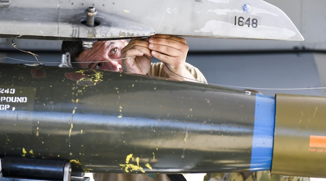 Staff Sgt. Matthew Perry, 309th Aircraft Maintenance Unit weapons load crew team chief, attaches an inert bomb on to an F-16C Fighting Falcon during the 3rd Quarter Load Crew Competition Oct. 17, 2019, at Luke Air Force Base, Ariz.