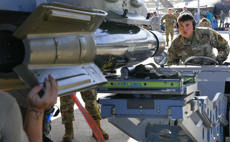 Senior Airman Calvin Hernandez, 309th Aircraft Maintenance Unit weapons load crew member, directs an inert munition from a jammer onto an F-16C Fighting Falcon during the 3rd Quarter Load Crew Competition Oct. 17, 2019, at Luke Air Force Base, Ariz.