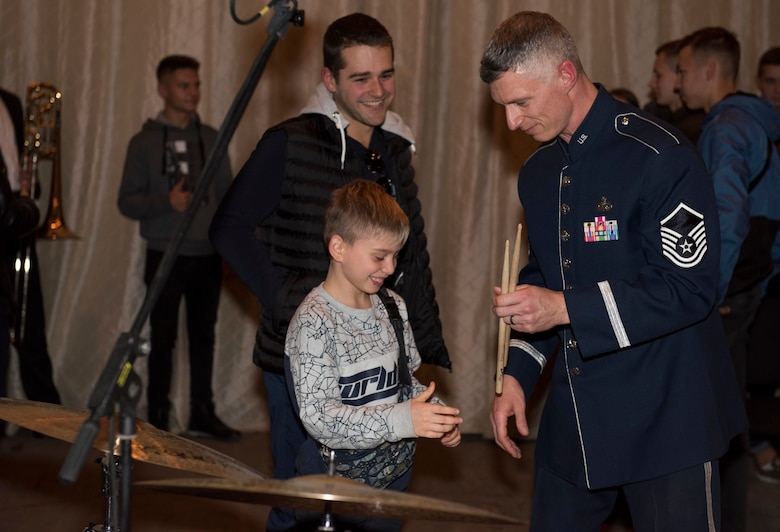 "U.S. Air Force Master Sgt. Tim Stombaugh, U.S. Air Forces in Europe Ambassadors Jazz Band drummer, hands drum sticks to a local music student during a master class with the USAFE Band and the Ukrainian National Presidential Orchestra at the Philharmonic in Chernivisti, Ukraine, Oct. 12, 2019. The USAFE Band traveled to six cities in central and western Ukraine October 6-20, 2019 to conduct the ""Music of Freedom"" tour, which celebrated the shared spirit of freedom and enduring partnership between U.S. and Ukrainian armed forces. (U.S. Air Force photo by Airman 1st Class Jennifer Zima)"