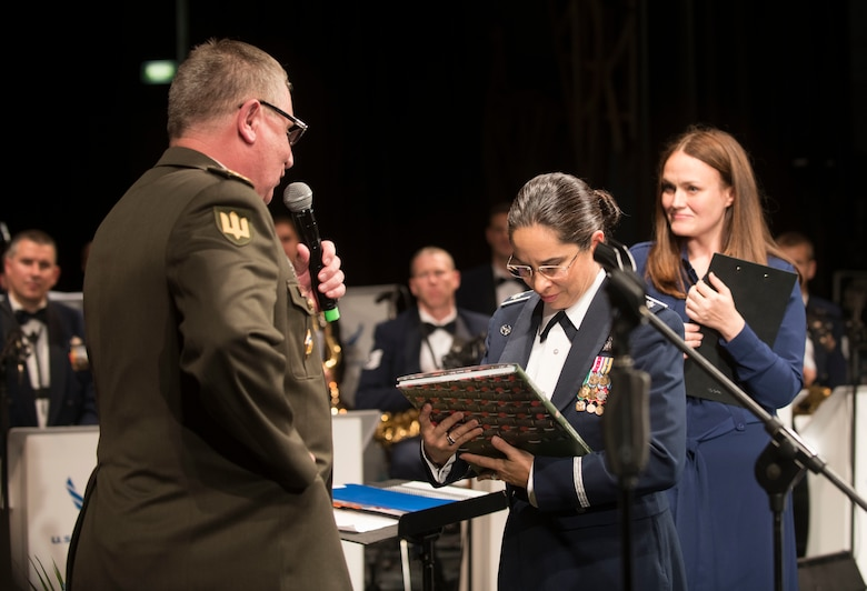 "U.S. Air Force Lt. Col Cristina Moore Urrutia, U.S. Air Forces in Europe Ambassadors Jazz Band commander and conductor, accepts a gift from National Ground Forces of Ukraine Lt. Gen. Pavlo Tkachuk, Chief of L'viv Garrison, after the USAFE Band performed a concert with the L'viv Opera Chamber Orchestra and Ukrainian National Presidential Orchestra at the Lviv National Opera, Lviv, Ukraine, October 9, 2019. The USAFE Band traveled to six cities in central and western Ukraine October 6-20, 2019 to conduct the ""Music of Freedom"" tour, which celebrated the shared spirit of freedom and enduring partnership between U.S. and Ukrainian armed forces. (U.S. Air Force photo by Airman 1st Class Jennifer Zima)"