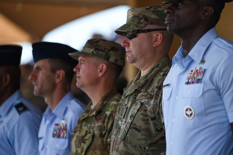 Col. Scovill Currin, 62nd Airlift Wing commander, second from left, and Chief Master Sgt. Rob Schultz, 62nd Airlift Wing command chief, third from left, observe a basic military training graduation parade on Lackland Air Force Base, Texas, Oct. 18, 2019. New basic military training graduates march in the graduation parade across the enlisted heroes walk at the end of their eight weeks of demanding training.