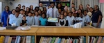 Ryan McLeod, DLA Troop Support Project G.I.V.E. coordinator, center, holds a cake and poses with students and tutors during the Project G.I.V.E. pizza party at the Benjamin Franklin Elementary School Oct. 1, 2019 in Philadelphia.