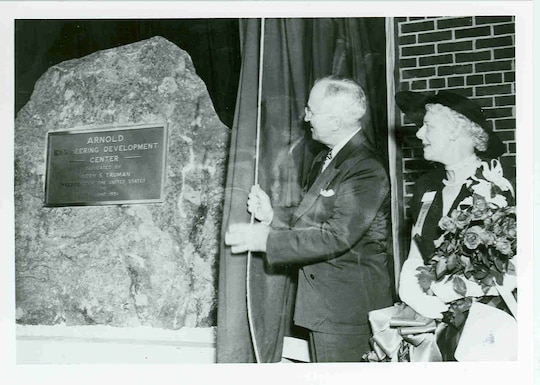 """During a June 25, 1951, ceremony at Arnold Air Force Base, President Harry Truman draws aside the curtain to reveal a dedicatory plaque mounted to a granite rock. The ceremony was held to dedicate the Air Engineering Development Center as the Arnold Engineering Development Center in honor of Gen. Henry H. """"Hap"""" Arnold, who had passed away before the ceremony and whose vision was instrumental in bringing the center to fruition. Pictured with Truman is Arnold's widow, Bee. It was 70 years ago this month that Truman signed into law the bills that allowed for the establishment of AEDC. (U.S. Air Force photo)"""