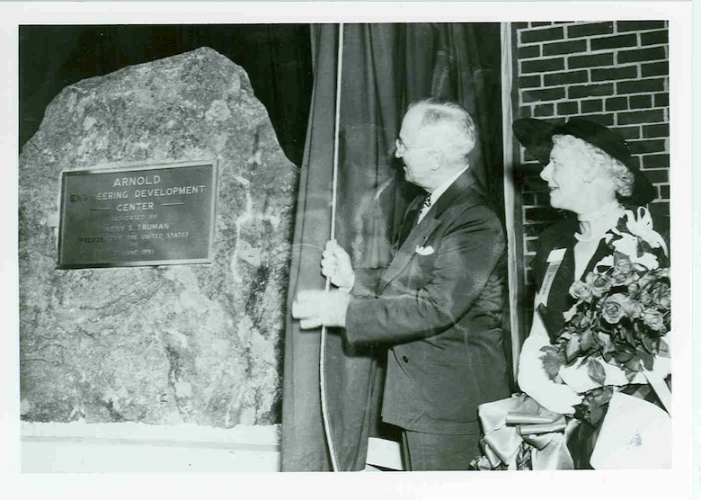 "During a June 25, 1951, ceremony at Arnold Air Force Base, President Harry Truman draws aside the curtain to reveal a dedicatory plaque mounted to a granite rock. The ceremony was held to dedicate the Air Engineering Development Center as the Arnold Engineering Development Center in honor of Gen. Henry H. ""Hap"" Arnold, who had passed away before the ceremony and whose vision was instrumental in bringing the center to fruition. Pictured with Truman is Arnold's widow, Bee. It was 70 years ago this month that Truman signed into law the bills that allowed for the establishment of AEDC. (U.S. Air Force photo)"