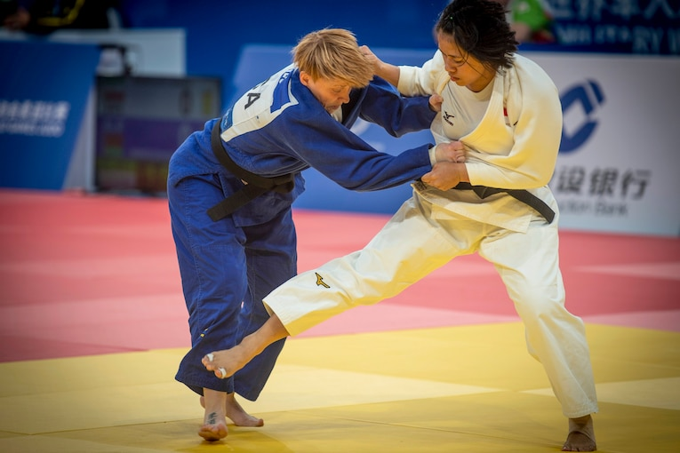 One woman holds onto a second woman who is trying to trip her during a judo match.