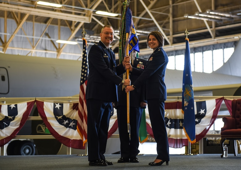 U.S. Air Force Col. Russel Davis, 92nd Operations Group commander, passes the 97th Air Refueling Squadron's guidon to Lt. Col. Cindy Dawson, 97th ARS incoming commander, during the squadron's reactivation ceremony and Assumption of Command at Fairchild Air Force Base, Washington Oct. 18, 2019.