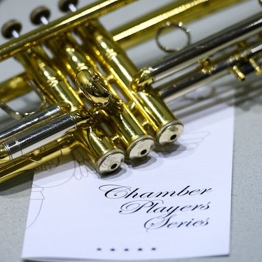 "A trumpet is pictured laying on its side on top of a concert program with the words ""Chamber Player Series"" printed in large letters on the front cover."