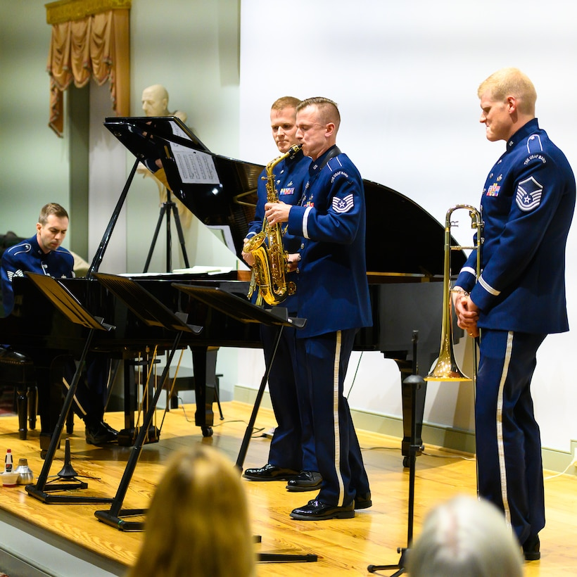 An Air Force alto saxophonist is seen flanked by two other members of the music ensemble as he performs a solo with a pianist who is seen in the far left of the picture. Each are wearing dark blue Air Force uniforms, and they are standing on a light colored wood stage.