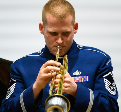 An Air Force trumpeter performs a solo using with a silver mute. He is wearing dark blue Air Force uniform against a white wall.