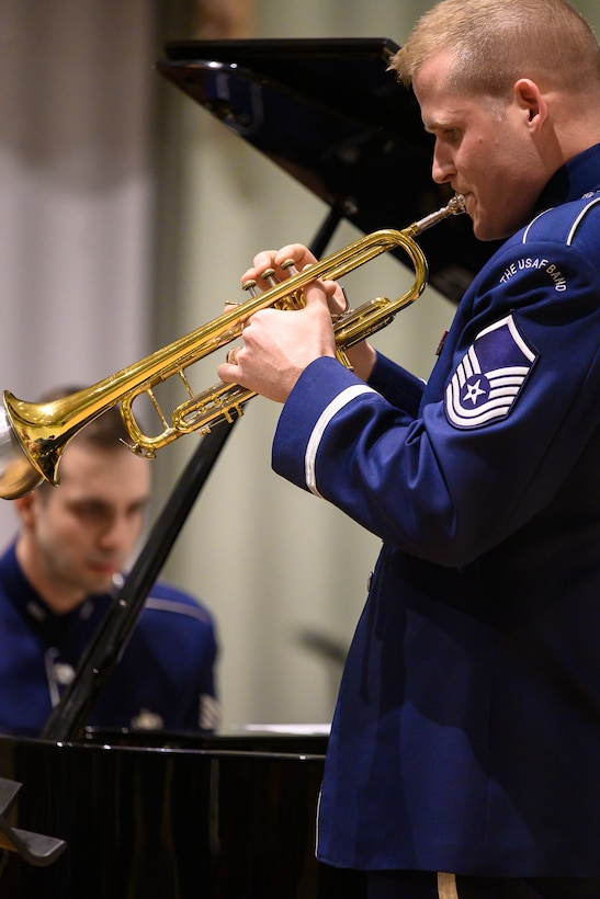 An Air Force trumpeter performs a solo and is pictures on the right, with a pianist who is seen in the far left of the picture. Each are wearing dark blue Air Force uniforms.