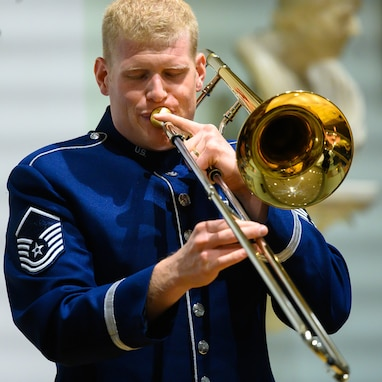 An Air Force trombonist performs a solo. He is wearing a dark blue Air Force uniform.