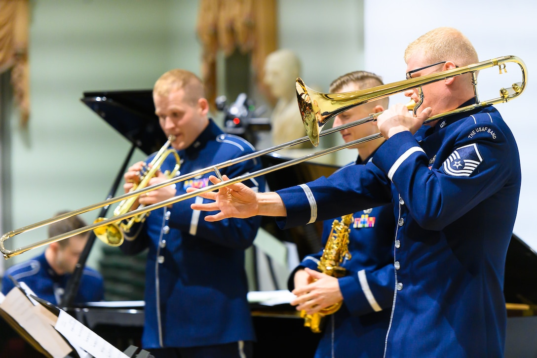Four Air Force musicians--a trombonist, trumpeter, saxophonist, and pianist--are performing. Each are wearing dark blue Air Force uniforms.