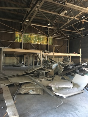 Debris from dismantled structures cover the floor of Building 844 at Travis Air Force Base, California, July 2, 2019. The refurbished hangar houses the new Nose Dock Gym, facilitated through existing base funds, equipment donations and volunteer work by the 60th Mission Support Group. (U.S. Air Force courtesy photo)