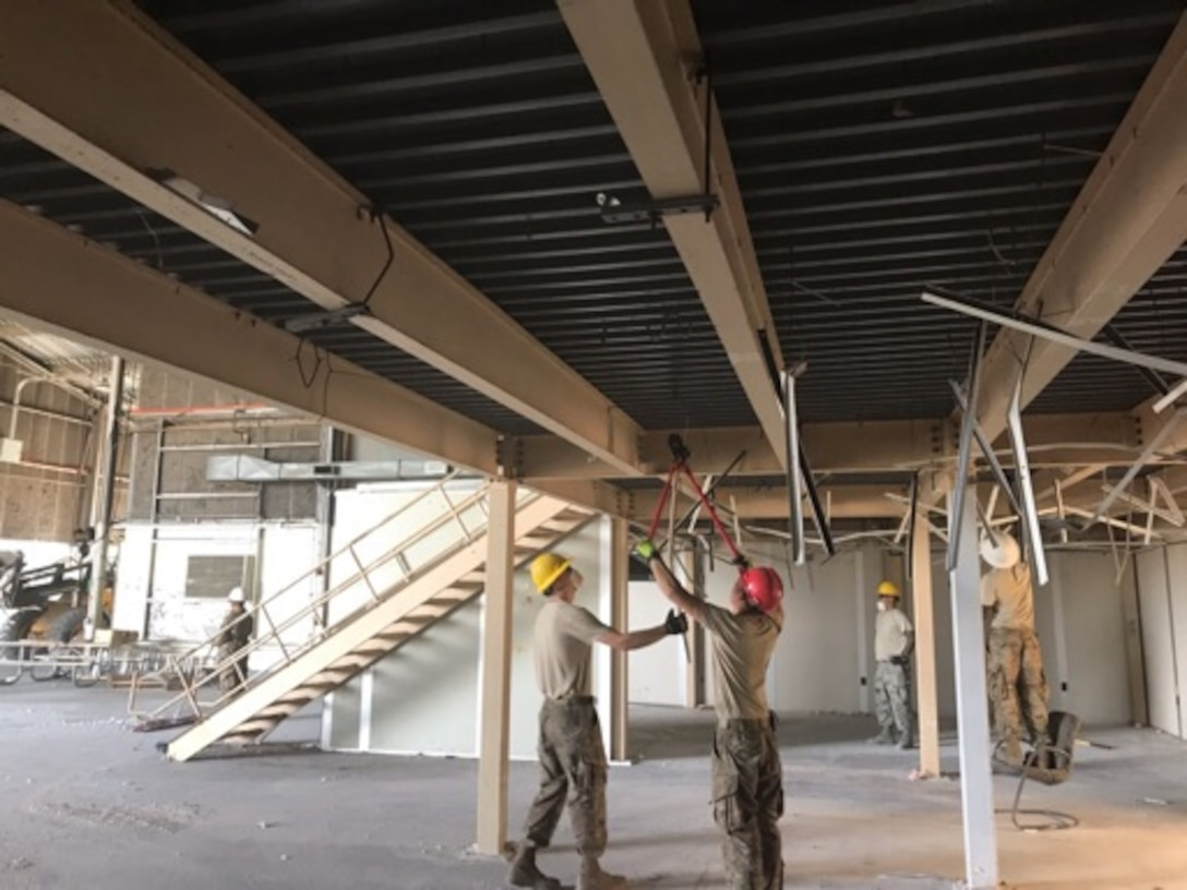 Crews from the 60th Civil Engineer Squadron structures shop dismantle old mobile offices inside Building 844 at Travis Air Force Base, California, July 2, 2019. The refurbished hangar houses the new Nose Dock Gym, facilitated through existing base funds, equipment donations and volunteer work by the 60th Mission Support Group. (U.S. Air Force courtesy photo)