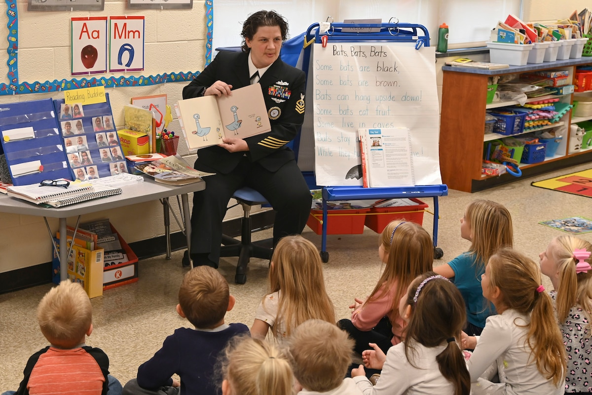 A sailor reads to a group of children.