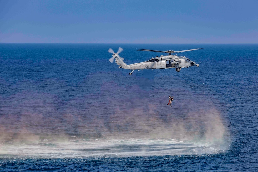 A low hovering helicopter kicks up sea spray from deep blue waters while hoisting service members on a line.