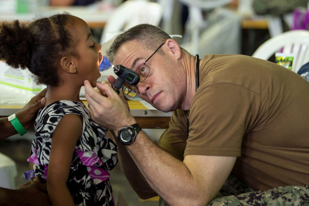 A Navy doctor uses a light to look into a girl's mouth.