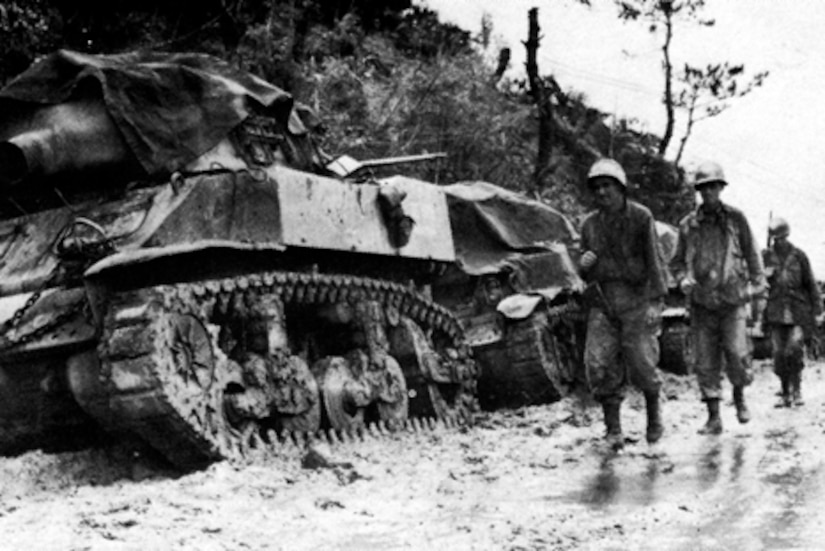 Soldiers trudge past tanks in the mud.