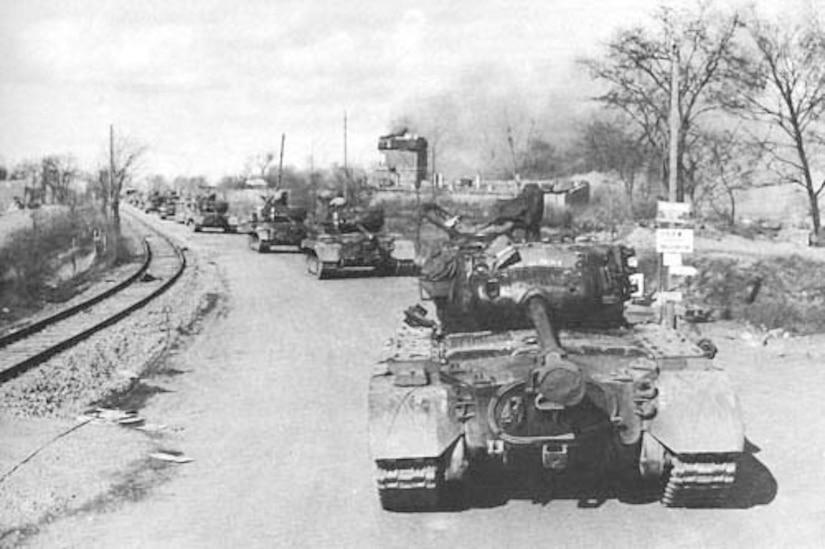 A tank convoy rolls down an empty street.