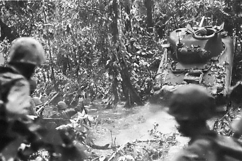 A tank emerges from a stream and up an embankment while several service members trail behind amid dense foliage.