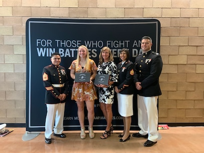 U.S. Marines with Recruiting Station San Diego present Mejan Janikowski and her mentor selection kits for the Semper-Fi All American Academy at Cathedral Catholic High School, May 1, 2019. The Battles Won Academy recognized students who are fighting and winning battles both on and off the playing field to make their communities and country stronger. (U.S. Marine Corps photo by Sgt. Bernadette Plouffe)