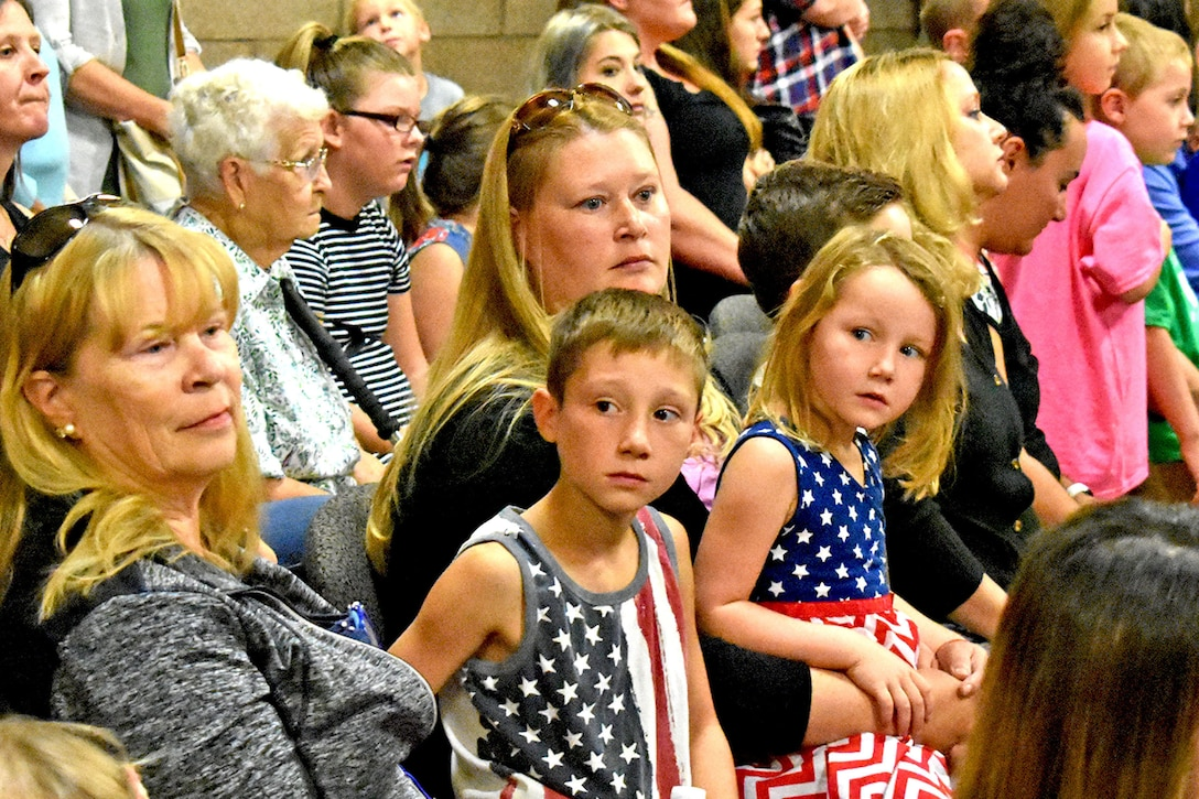 Young children and parents are seated as members in an audience.