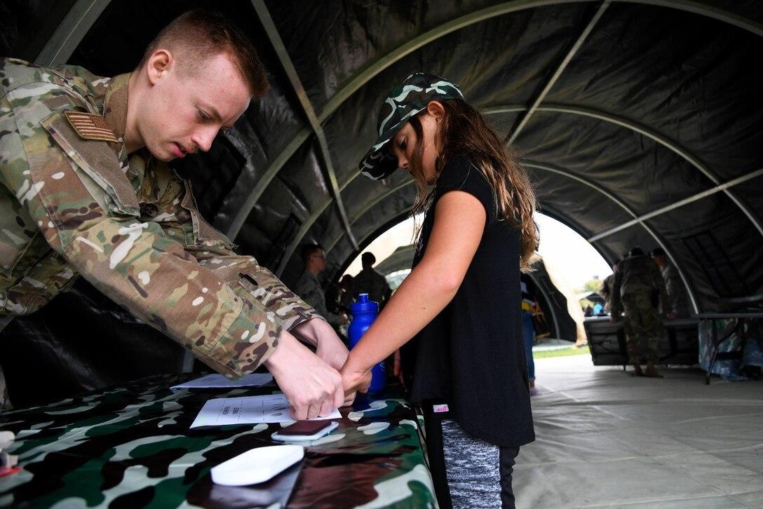 A man in a military uniform fingerprints a young girl.