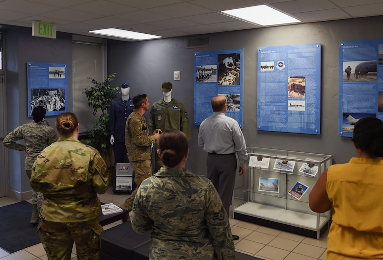Team McChord Airmen and civilians peruse displayed items and wall hangings in the newly updated Heritage Hall in the wing headquarters building at Joint Base Lewis-McChord, Wash., Oct. 21, 2019. The newly updated hall features Team McChord's heritage in past operations while also highlighting the men and women serving now at McChord. (U.S. Air Force photo by Senior Airman Tryphena Mayhugh)