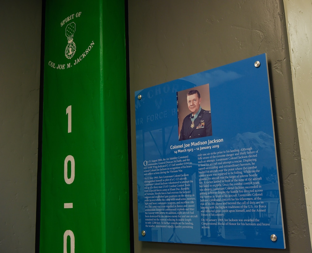 A commemorative plaque hangs on the wall in the newly updated Heritage Hall in the wing headquarters building honoring retired Col. Joe Jackson, Air Force Medal of Honor recipient, at Joint Base Lewis-McChord, Wash., Oct. 21, 2019. In 2006, a McChord C-17 Globemaster III was dedicated to Jackson in recognition of his actions during the Vietnam War. (U.S. Air Force photo by Senior Airman Tryphena Mayhugh)