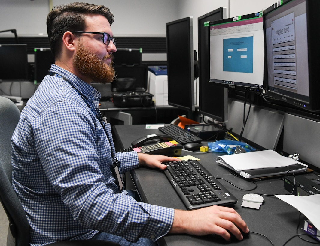 Gareth Penfold, an instrumentation, data and control engineer, views the digital database he created to track calibration requirements for test, measurement and diagnostic equipment used in the AEDC Aerodynamic and Propulsion Test Unit at Arnold Air Force Base. The calibration records were previously kept in binders, then moved to a spreadsheet and now are tracked via the database created by Penfold. (U.S. Air Force photo by Jill Pickett) (This image has been altered by obscuring badges for security purposes.)