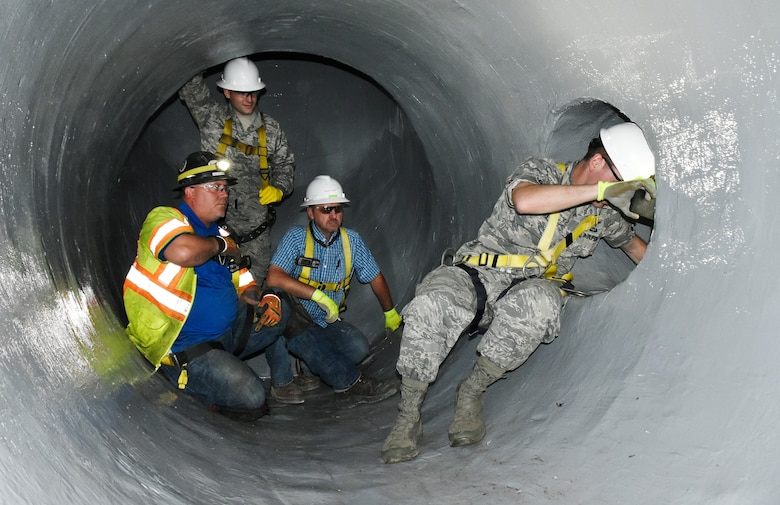 Dusty Pickens, from left, 2nd Lt. Adam Doyle and Andy Crum look on as Maj. Michael Knauf exits a 30-inch pipe in the raw water pipe system at Arnold Air Force Base. The group conducted an inspection of pipes recently lined with a fiber-reinforced polymer, Sept. 23. (U.S. Air Force photo by Bradley Hicks)