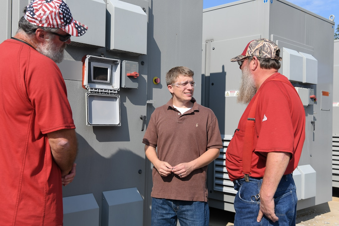 "Electricians Lon Britt, left, and Robert Campbell, right, along with electrical engineer Adam Webb look at a rectifier, like one that was responsible for an un-commanded ""runaway"" condition, outside the AEDC Aerodynamic and Propulsion Test Unit at Arnold Air Force base. Webb improved the logic used in the Programmable Logic Controllers on the units to handle un-commanded ""runaways,"" which allowed him to identify the part at fault. (U.S. Air Force photo by Jill Pickett) (This image has been altered by obscuring items for security reasons.)"