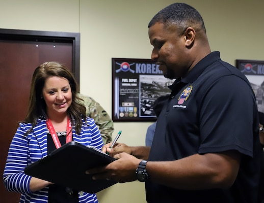 Molly Capps, principal of McDeeds Creek Elementary School in Carthage, N.C., left, signs for the computers donated to her school by U.S. Army Forces Command from Eric Garris, Defense Logistics Agency, Oct. 15.