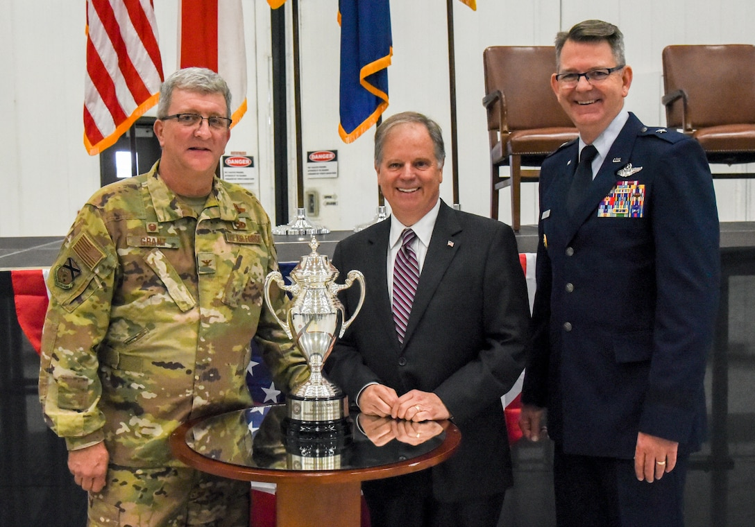 """Col. Robert """"Scott"""" Grant, commander, 117 Air Refueling Wing, Sen. Doug Jones and Brig. Gen. James R. Stevenson Jr., Mobilization Assistant to the Director of Operations United States Strategic Command, pose with the Omaha Trophy at Sumpter Smith Air National Guard Base, AL., Oct. 19, 2019.  Jones attended the ceremony and Stevenson presented the trophy celebrating the 117 ARW winning the award having won it in the startegic aircraft category.  The unit was the first Air National Guard tanker unit to win the award(U.S. Air National Guard photo by Master Sgt. Jeremy Farson)"""