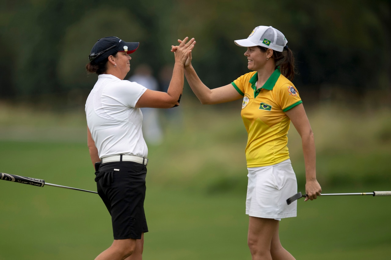 An Air Force golfer high-fives a Brazilian golfer on a course.