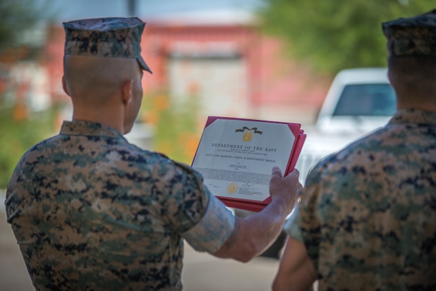 U.S. Marines with the Provost Marshalls Office, Headquarters and Headquarters Squadron, Marine Corps Air Station (MCAS) Yuma, are awarded the Navy and Marine Corps Achievement Medal on MCAS Yuma, Oct 2, 2019. The Marines were awarded the Medal for their heroic actions following a traffic accident. (U.S. Marine Corps photo by Lance Cpl John Hall)