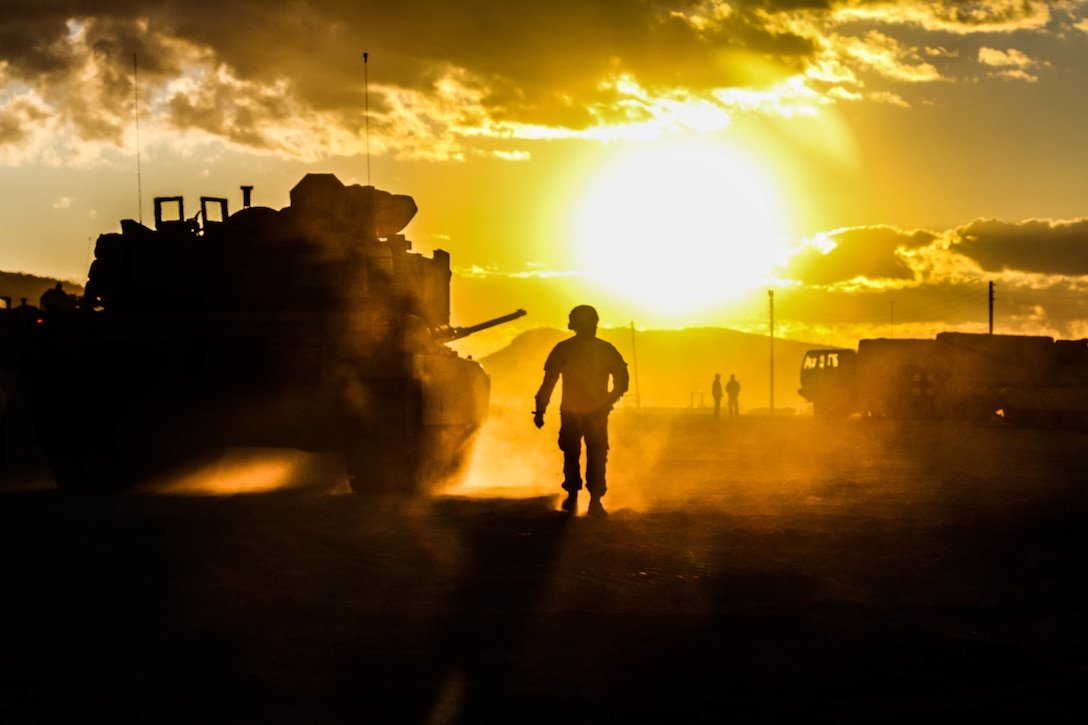A soldier walks in between two tanks with a bright yellow glow coming from the sun in the background.